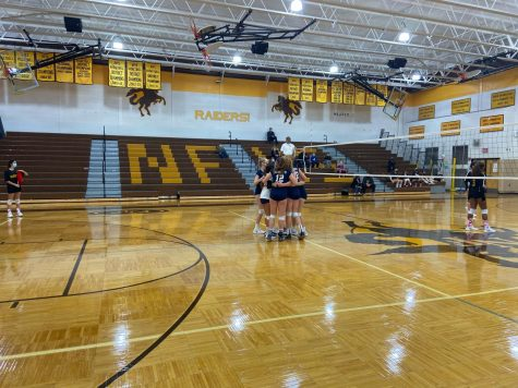 The Freshman Berkley Volleyball team huddling during their game.